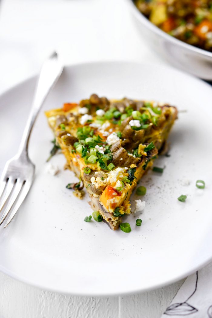 Slice of Roasted Pumpkin Kale and Feta Frittata on white plate.