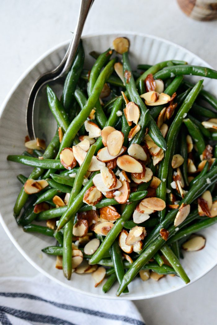 cream bowl of garlicky green beans almondine with spoons.