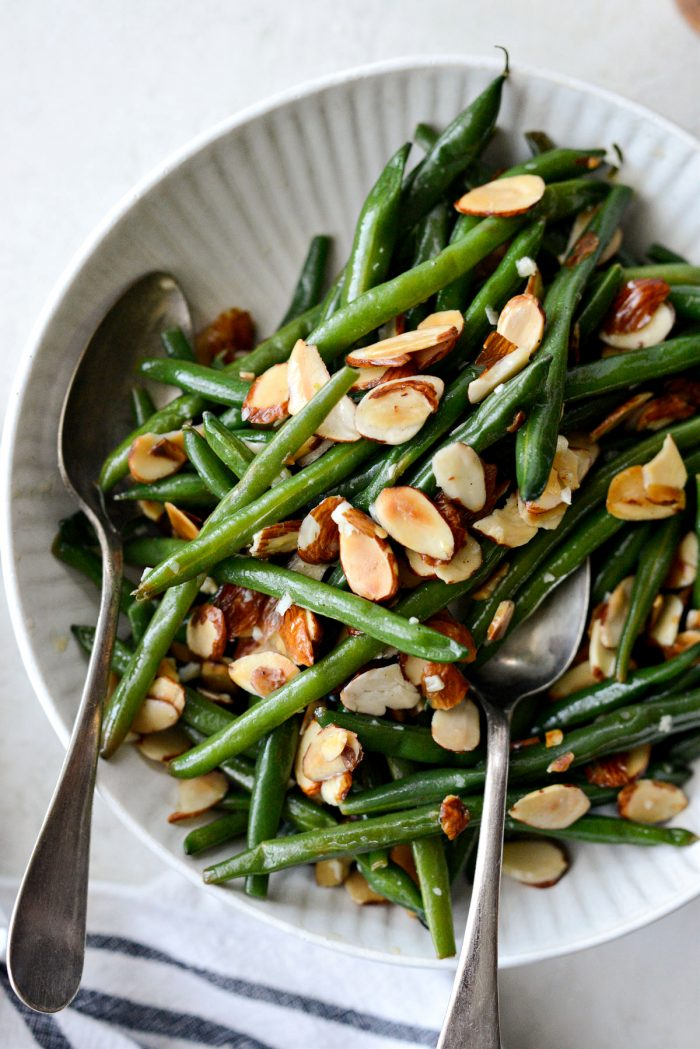 garlicky green beans almondine in cream colored bowl.