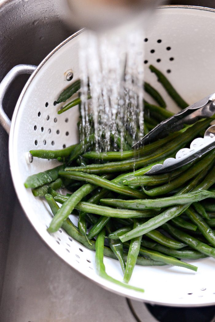 rinsing blanched green beans with cold water.