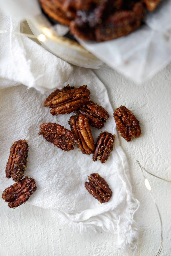 scattered Honey Vanilla Bourbon Pecans on a white linen napkin.