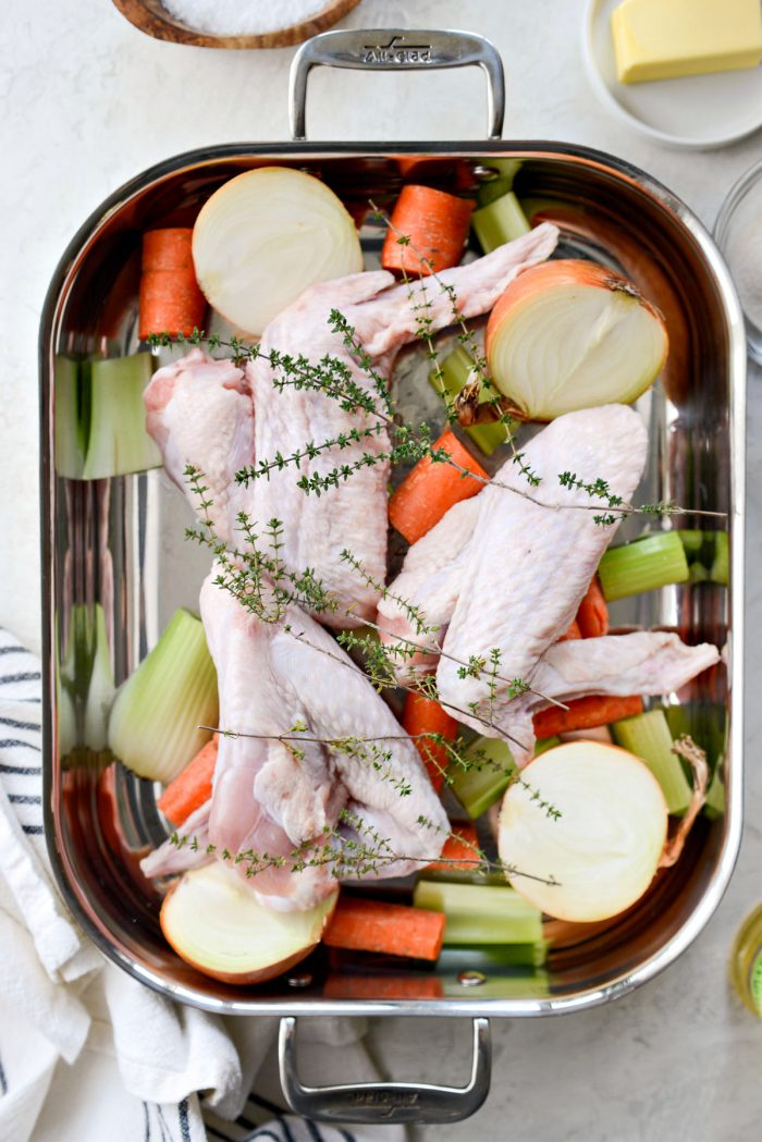 roasting pan with vegetables, herbs and turkey wings.