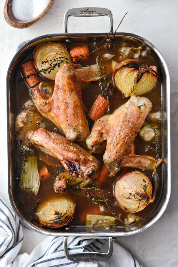 reduced broth in roasting pan with turkey, vegetables and thyme.