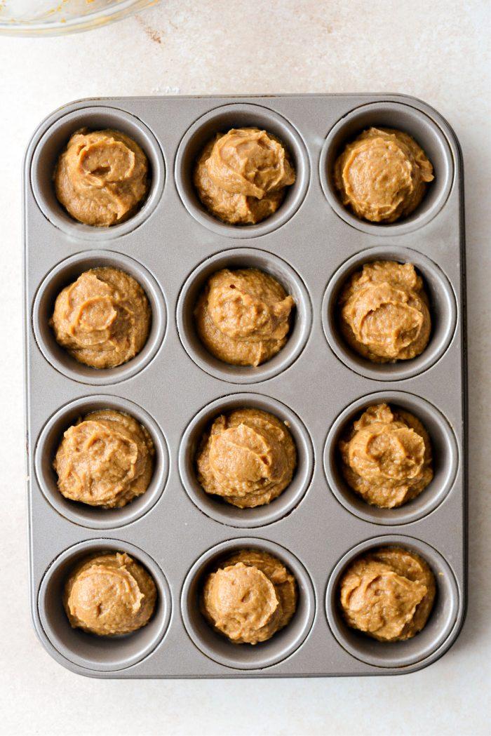 pumpkin pie batter divided among muffin tin.