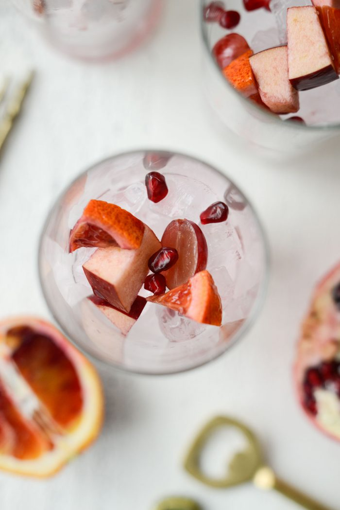 ice and some fruit to glasses.