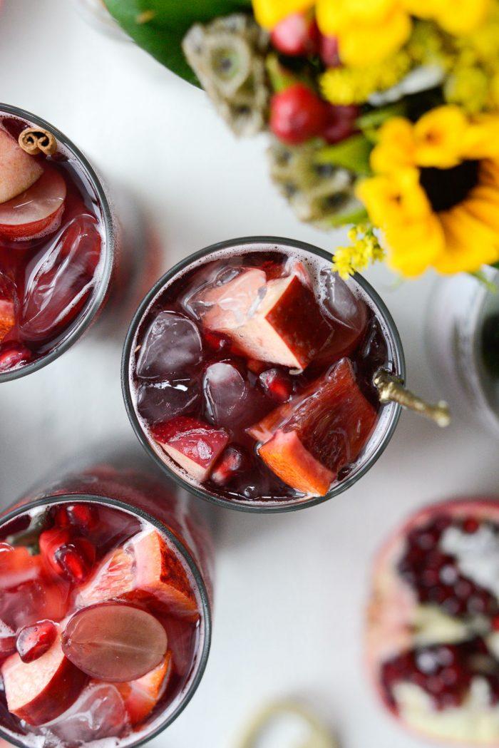 close up of fruit in glass of pomegranate sparkling apple cider sangria.