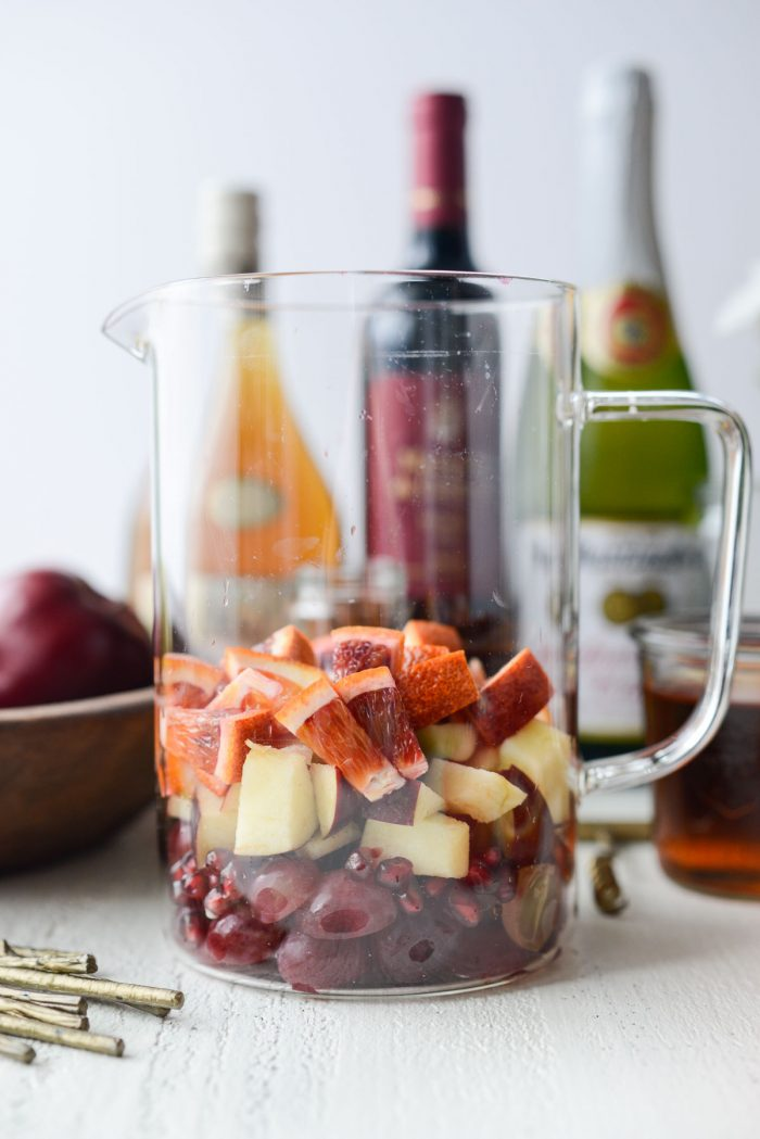 grapes, pomegranate arils, apples and blood oranges in a glass pitcher.