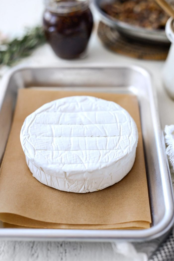 top of brie is scored and then placed on parchment paper