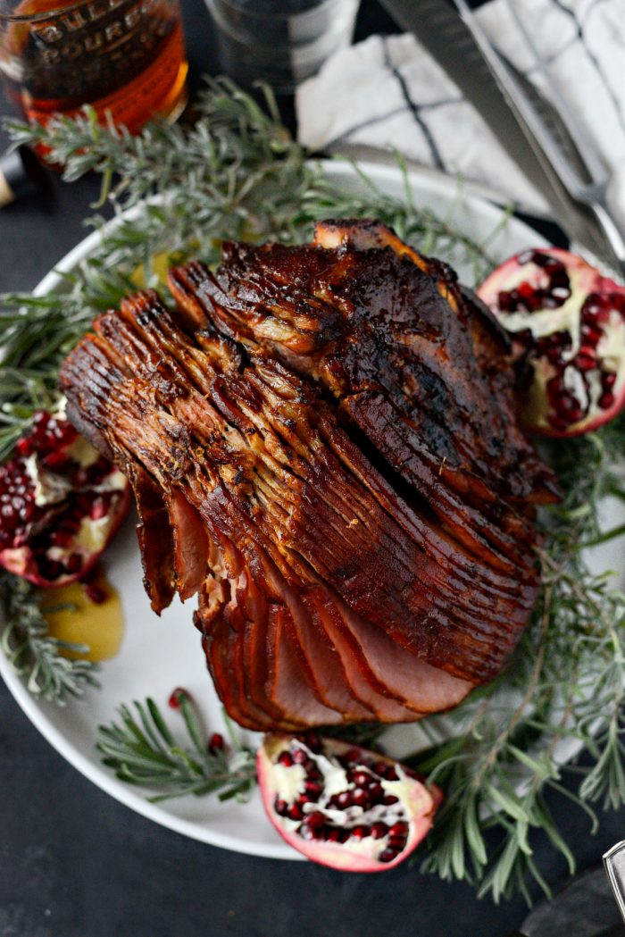 Pomegranate Bourbon Glazed Ham on platter with pomegranate halves