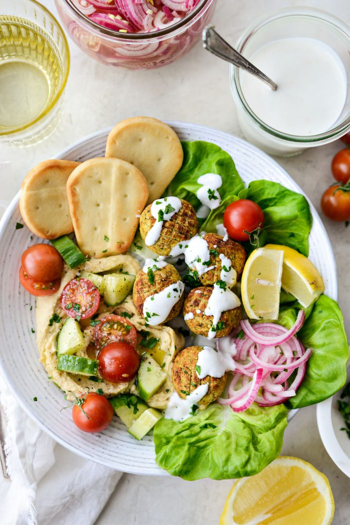 Air Fryer Falafel in a white bowl with pickled red onion and lemon
