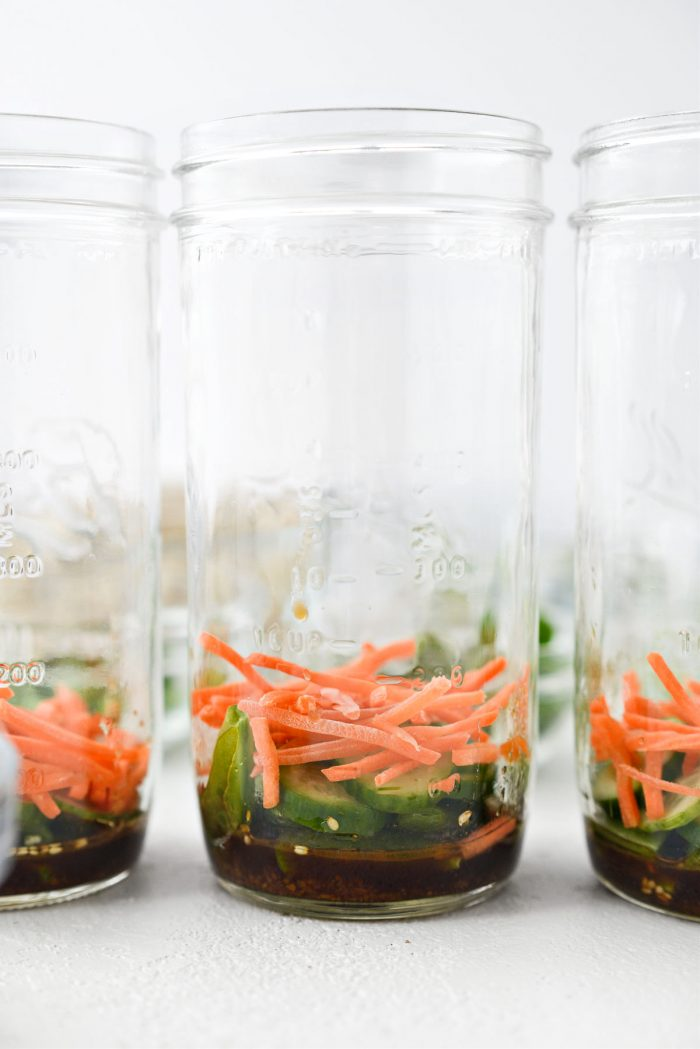 mason jar with dressing, snap peas, cucumber and carrots.