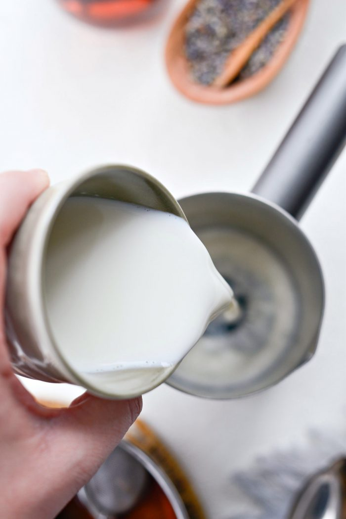 pour milk and vanilla syrup into frother