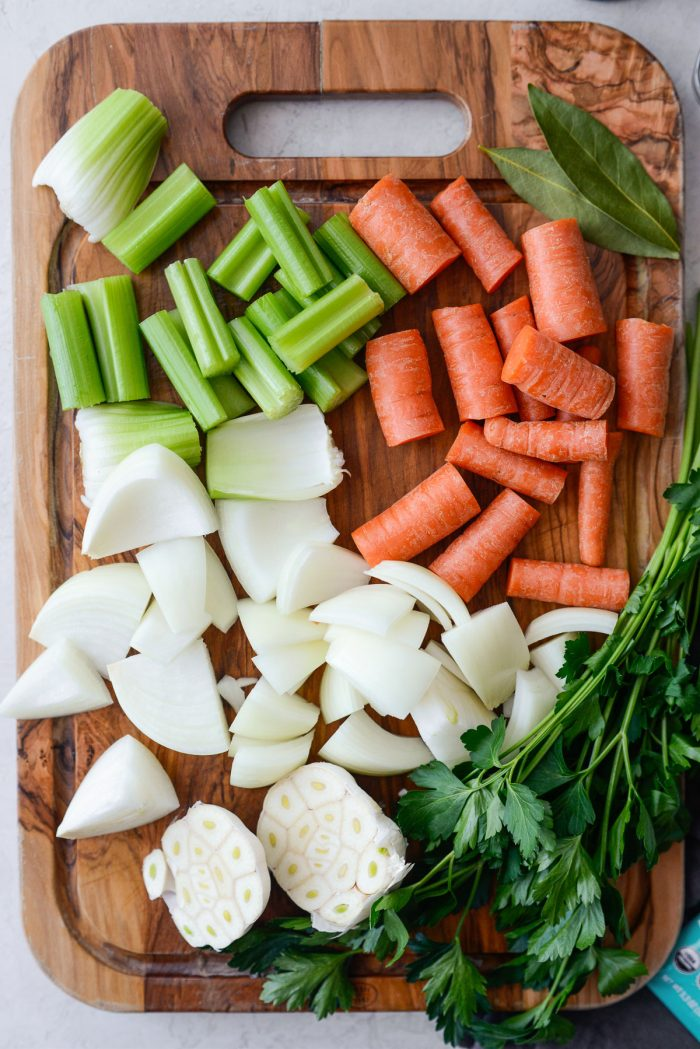 roughly chopped onion, carrots and celery with herbs and halved garlic.