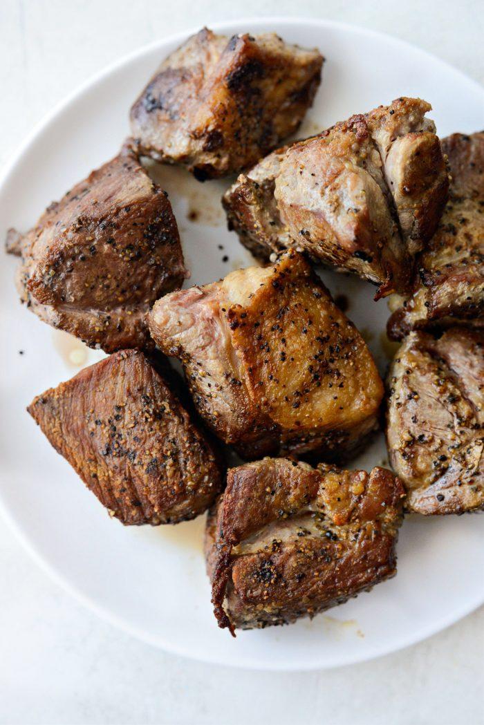 seared pork on a white plate.