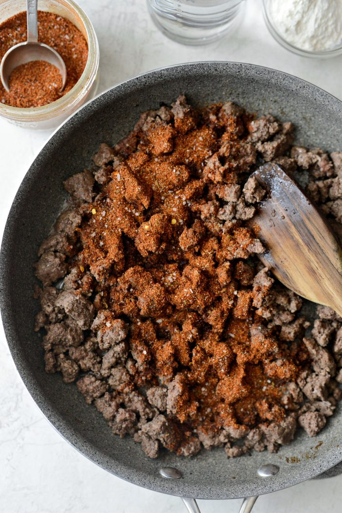 taco seasoning sprinkled over cooked ground beef