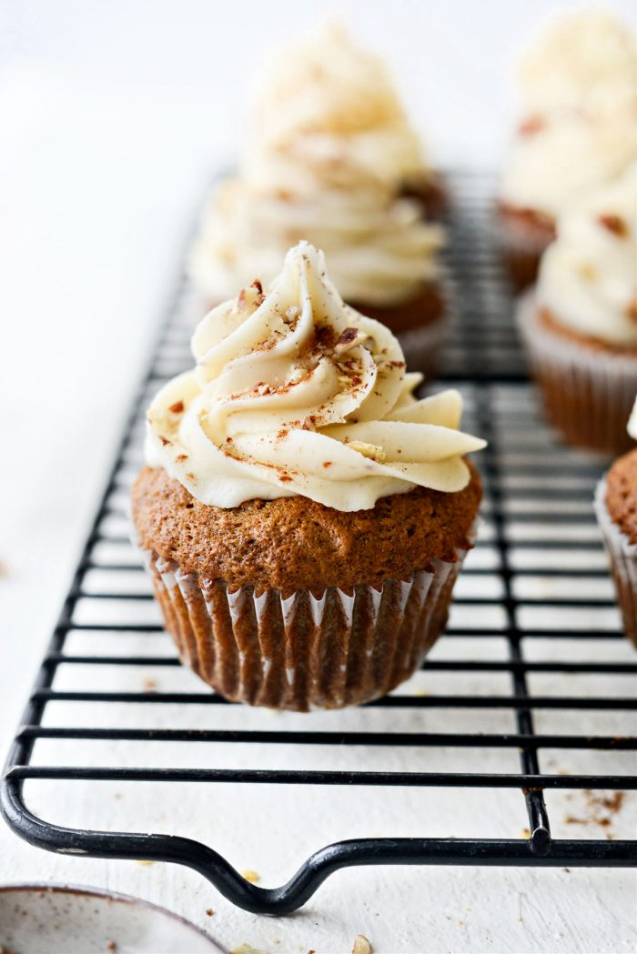 Garnish Carrot Cake Cupcakes with ground cinnamon and chopped pecans.