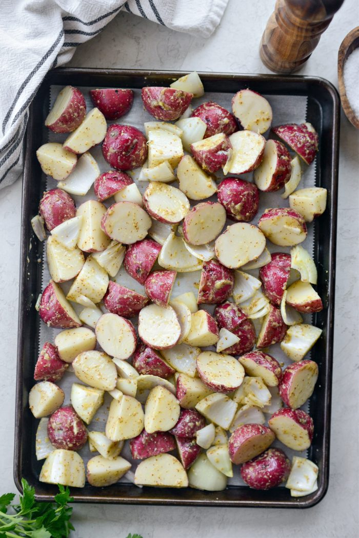 spread onions and potatoes onto parchment paper lined sheet pan