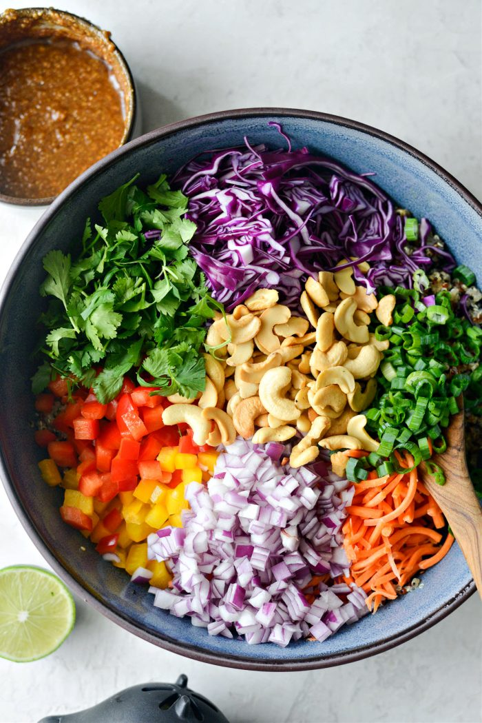 cabbage, cilantro, peppers, onion carrot, cashews and green onion in bowl with quinoa