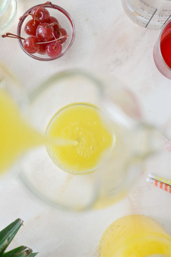 pouring pineapple juice into pitcher