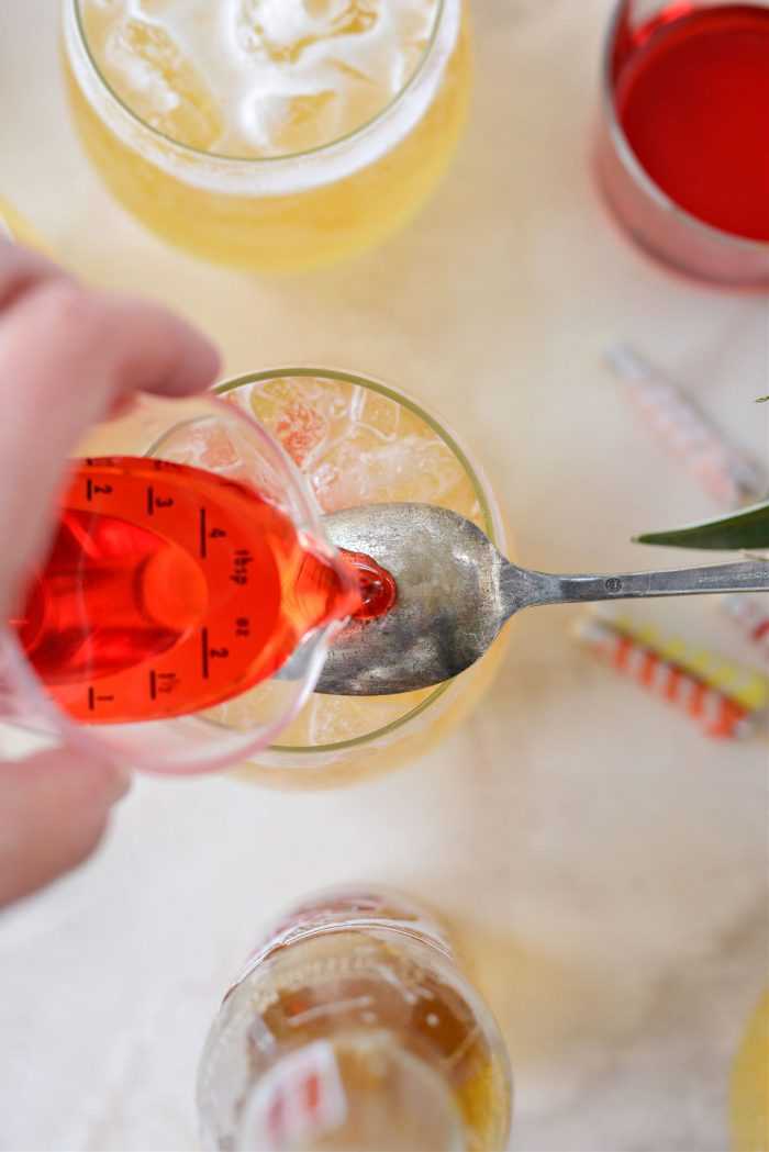 pouring grenadine over back of spoon