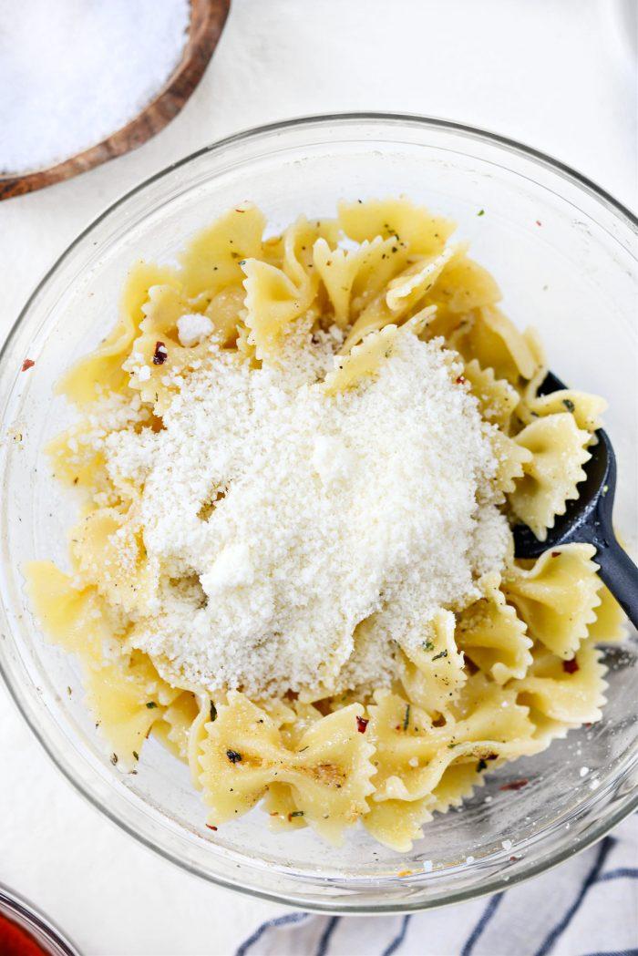 grated pecorino romano added to seasoned pasta
