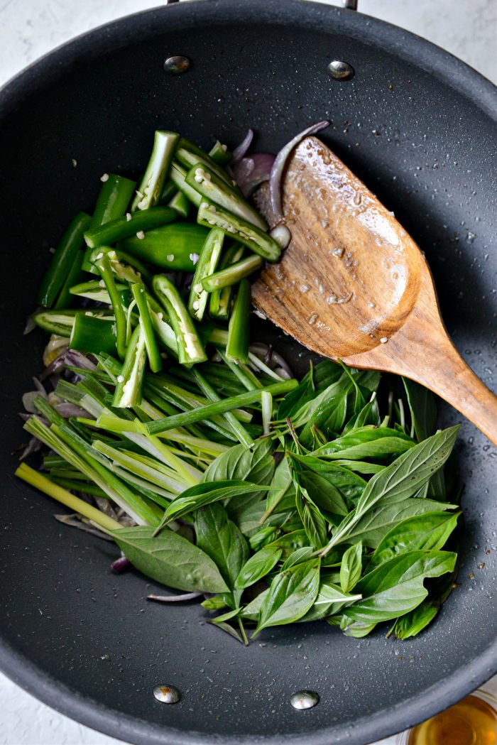 adding serrano, julienned green onion, thai basil to pan