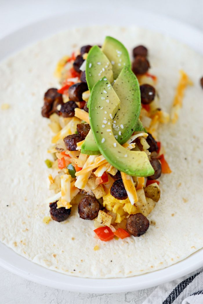 eggs, cheese, sausage, pepper and onions and avocado on a tortilla